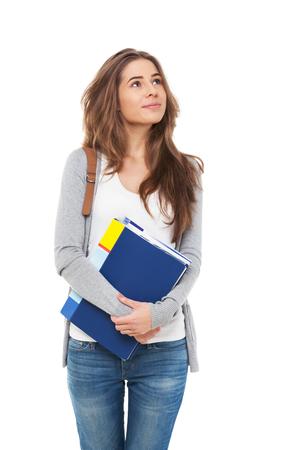 Jonge gelukkige vrouwelijke student op zoek op zoek up op wit wordt geïsoleerd.