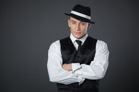 gangster background: Young male confident male posing in gangster style suite. Studio isolated on gray background. Stock Photo