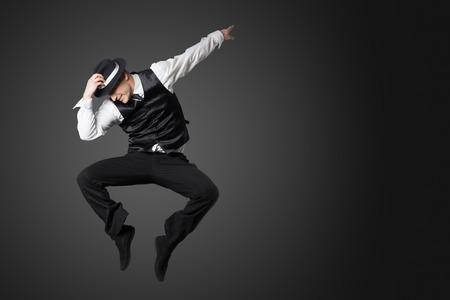 Jonge mannelijke professionele danser dansen in de studio op een grijze achtergrond.