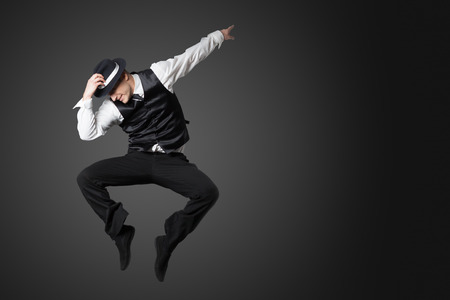 Young male professional dancer dancing in studio isolated on gray background.