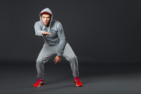fullbody: Fullbody portrait of young cool man dancing on dark gray background. Stock Photo