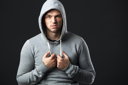 Studio portrait of brutal looking young guy in sportswear.