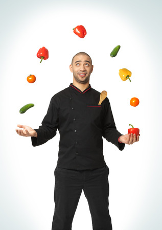 juggling: Afro American professional cook juggling vegetables - isolated on white background.