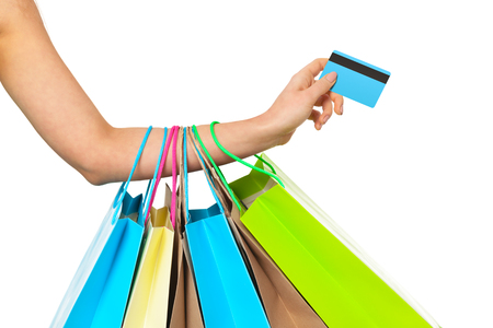 shopping card: Close up of womans hand with shopping bags and credit card isolated on white background. Shopping concept. Stock Photo