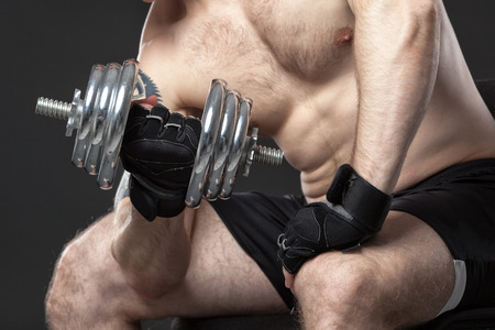 powerfully: Muscular yong man exercising with dumbbell on grey background Stock Photo