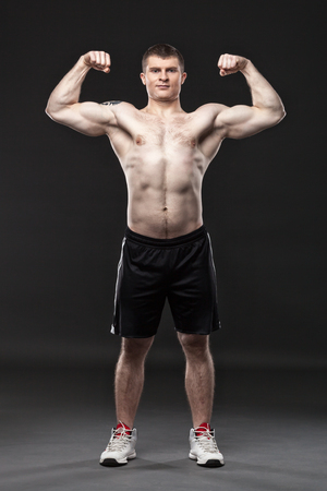 muscular body: Sporty and healthy muscular man isolated on black background Stock Photo