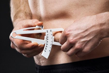 no body: Young man is measuring his body fat with calipers.