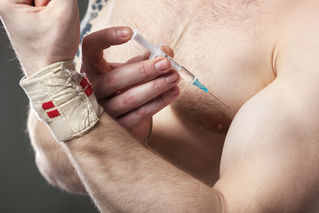 hormone  male: Close up of a muscular man injecting himself with steroids.