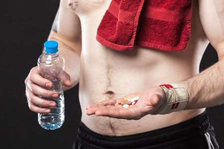 fat burning: Young man holding a different colored pills on a black background Stock Photo