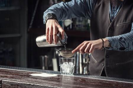 straining: Barman makes cocktails with a shaker.