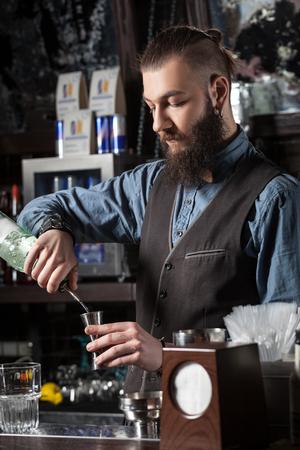 barman: Barman pouring alcohol to the metal jigger.