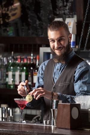 barman: Happy young barman serving cocktail at the bar.