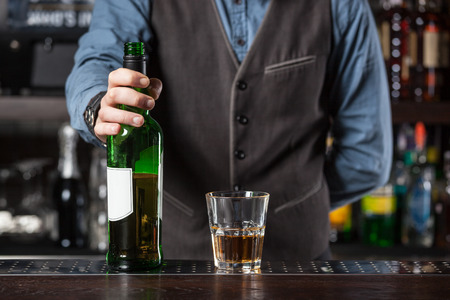 booze: Barman giving whiskey glass with booze and bottle- concept image.