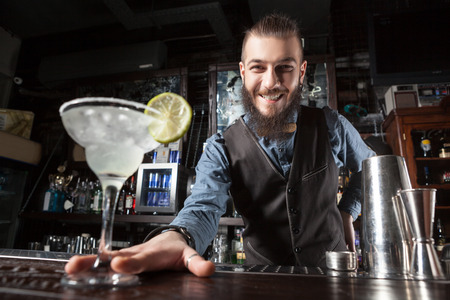 This is a photograph of barman serving cocktail margarita. Foto de archivo