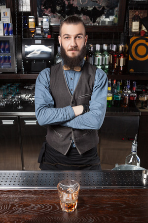 man style: Confident Barman serving cocktail at the bar.