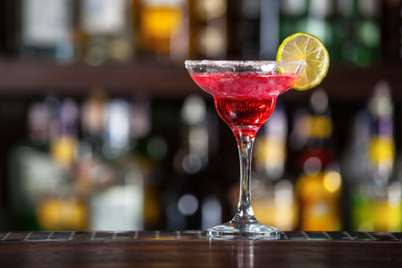 fruit of the spirit: Cocktail garnished with lime standing on the bar counter. Stock Photo