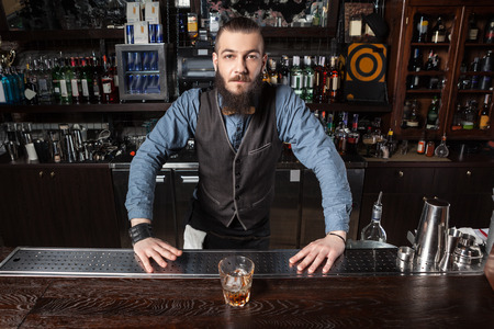 cocktail bar: Confident Barman serving cocktail at the bar.