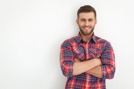 beau mec: Portrait de jeune homme debout contre un mur blanc beau.