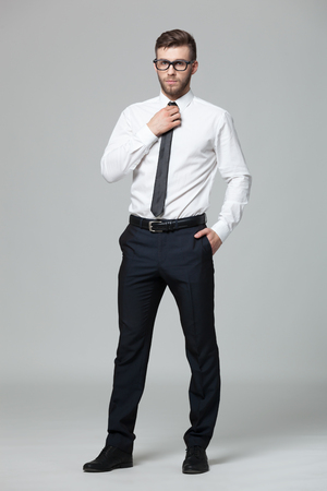 black fashion model: Portrait of handsome young businessman standing against gray background.