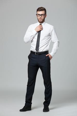 Portret van knappe jonge zakenman tegen grijze achtergrond. Stockfoto