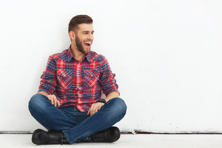 Portrait of happy surprised handsome young man in casual wear sitting against white wall.