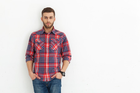 llanura: Portrait of handsome young guy standing against white wall.