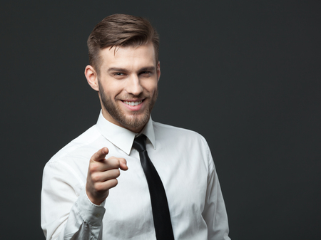 white suit: Hey  You! Young handsome businessman pointing at you while isolated on gray background. Stock Photo