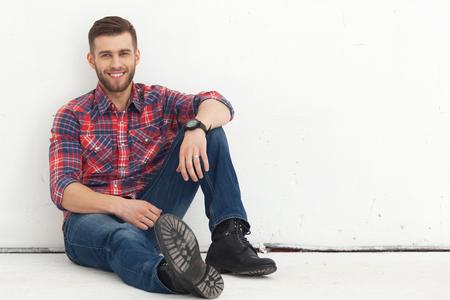 Portrait de jeune homme heureux beau dans des vêtements décontractés assis contre un mur blanc. Banque d'images