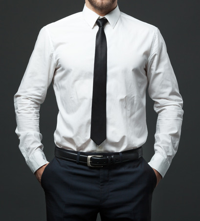 belts: Midsection of fit young businessman standing in formal white shirt, black tie and pants. Stock Photo