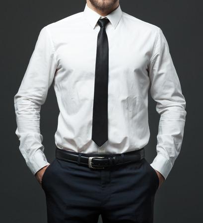 Sección media de hombre de negocios joven en forma de pie con la camisa blanca formal del lazo negro y los pantalones.