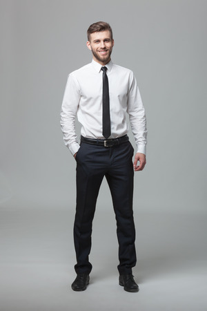 standing businessman: Portrait of handsome young businessman standing against gray background.