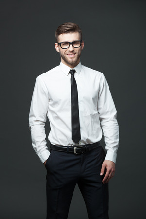 white men: Portrait of handsome young businessman standing against dark gray background.