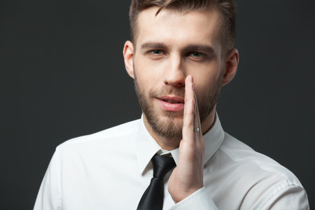 Jusy don`t tell anyone! Young businessman whispering trade secrets isolated on dark gray background.