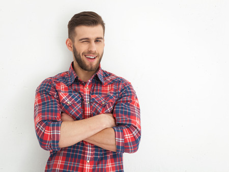 winking: Portrait of handsome young guy standing against white wall.