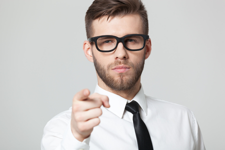 stylish men: Hey  You! Young handsome businessman pointing at you while isolated on gray background. Stock Photo