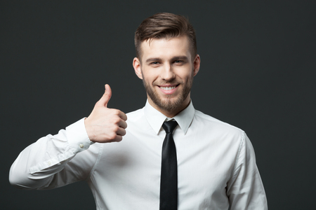 Everything is alright! Young handsome businessman showing thumbs up sign isolated on dark gray background.