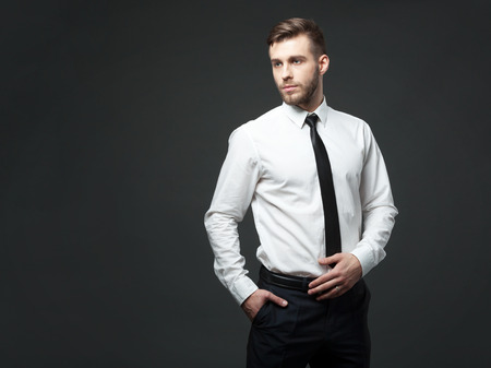 I am cool and successful! Studio portrait of handsome young businessman posing against gray background.