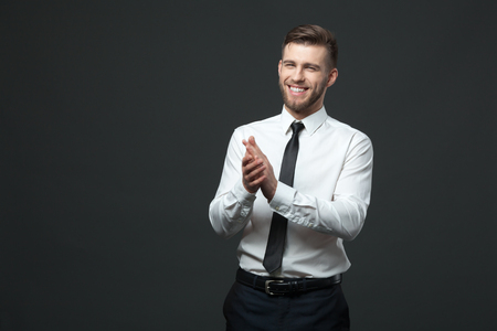 young businessman: Studio portrait of young happy handsome businessman claping hands isolated on dark background. Stock Photo
