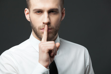 hearsay: Keep your secrets! Studio portrait of young handsome businessman gesturing shh to the camera. Stock Photo