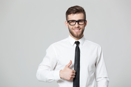 alright: Everything is alright! Young handsome businessman showing thumbs up sign isolated on gray background.