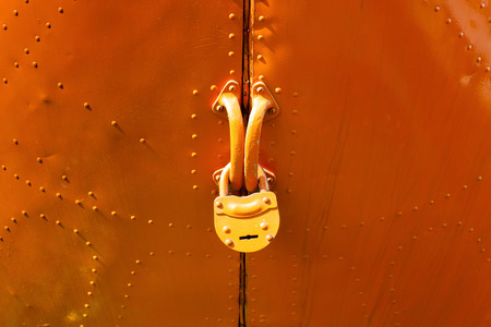 aircraft rivets: Old pained padlock on orange door  close up. Stock Photo