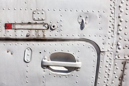 air plane: Old white painted aircraft fuselage close up. Door handle and rivets.