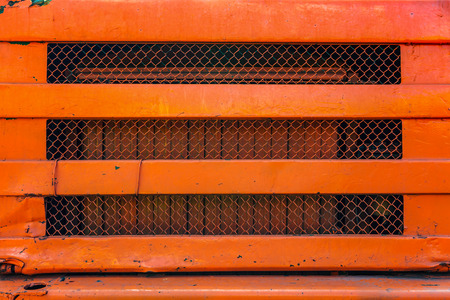 grille: Old orange painted truck grille close up. Stock Photo