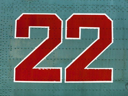 aluminum airplane: Old red 22 numbers on aircraft fuselage close up.