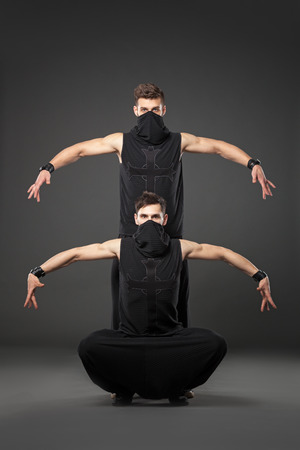 dance studio: Two male dancers dancing in ninja costumes against gray background. Stock Photo
