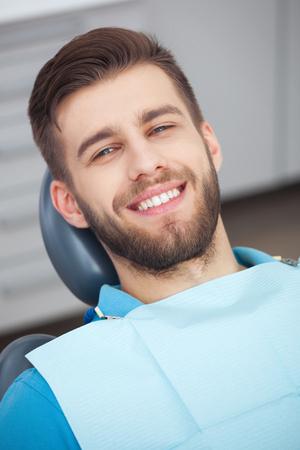 Mi sonrisa es perfecta! Retrato del paciente feliz en silla dental. Foto de archivo - 59456027