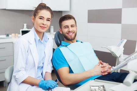 hombres jovenes: Mi dentista es la mejor! Retrato de una mujer dentista y el hombre joven en una oficina del dentista. Foto de archivo