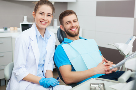 My dentist is the best! Portrait of a female dentist and young man in a dentist office.