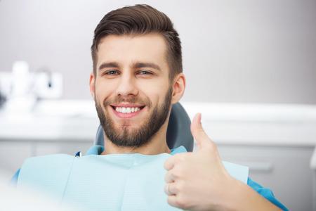 Mój uśmiech jest doskonały! Portret szczęśliwym pacjenta na fotelu dentystycznym.