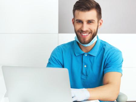 Portret van jonge mannelijke tandarts het werken met een notebook.